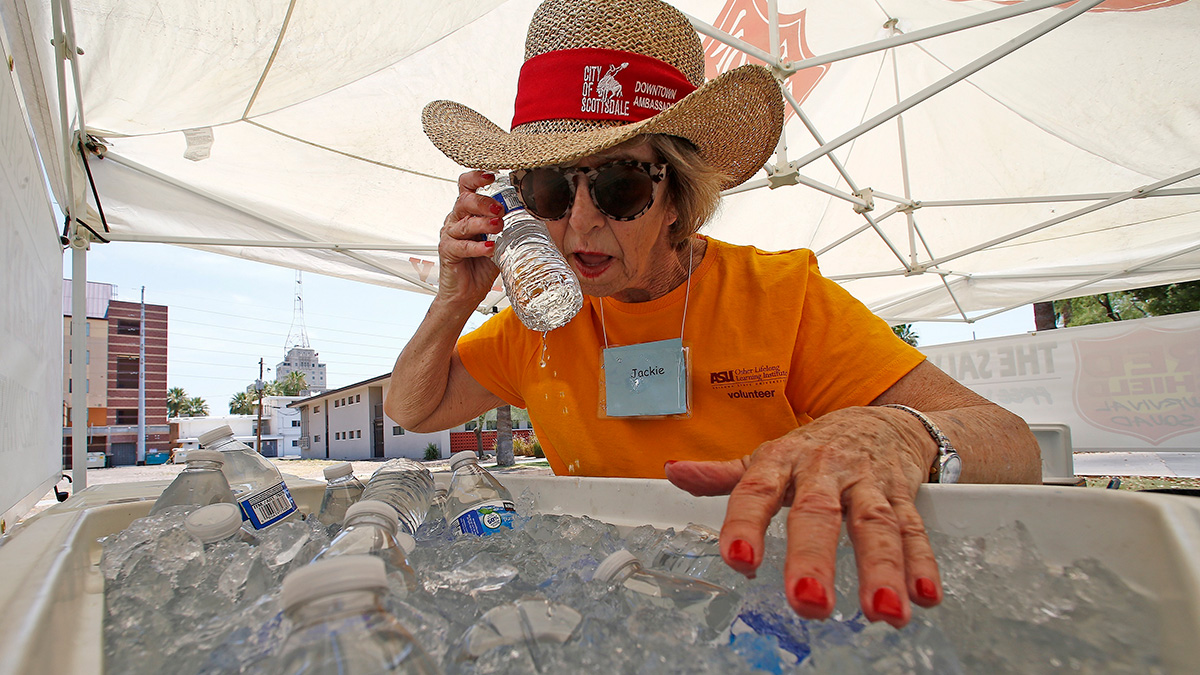 Salvation Army volunteer Jackie Rifkin tries to keep cool at she works at a special Salvation Army hydration station to help people try to keep hydrated and stay cool as temperatures climb to near-record highs, Monday, June 19, 2017, in Phoenix.