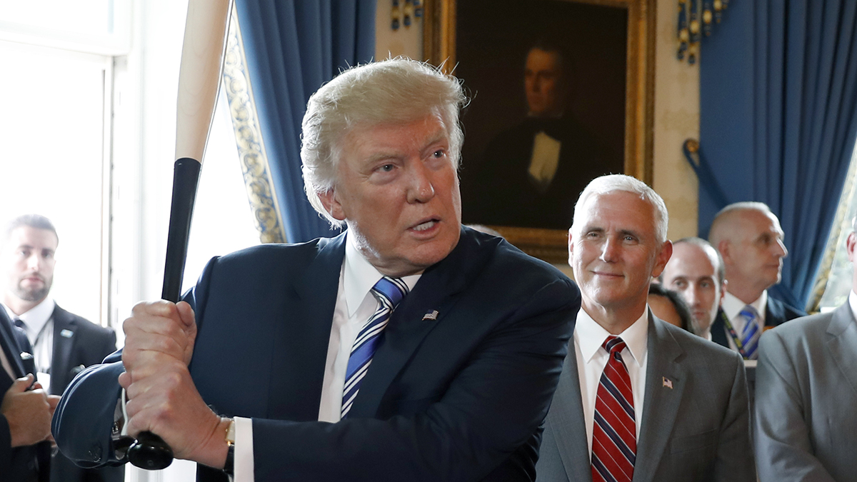 President Donald Trump prepares to swing a Marucci bat, from Baton Rouge, Louisiana, with Vice President Mike Pence, at right, during a