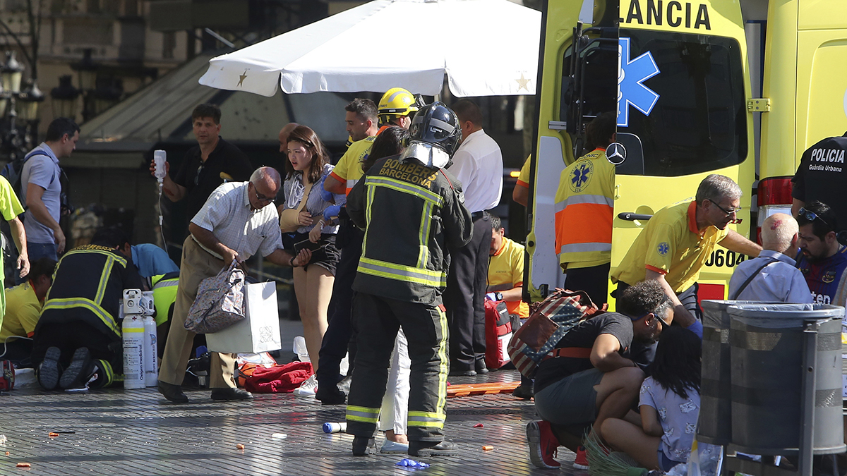 Injured people are treated in Barcelona, Spain, Thursday, Aug. 17, 2017, after a white van jumped the sidewalk in the historic Las Ramblas district, crashing into a summer crowd of residents and tourists and injuring several people, police said.