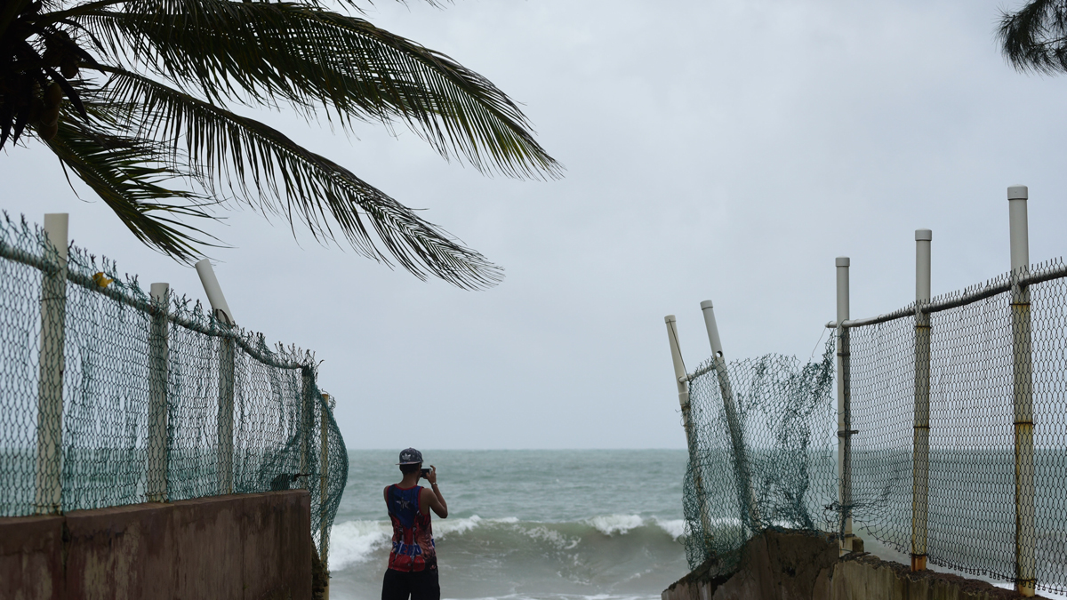 A man photographs the ocean before the arrival of Hurricane Irma, in luquillo, Puerto Rico, Wednesday, Sept. 6, 2017. Irma roared into the Caribbean with record force early Wednesday, its 185-mph winds shaking homes and flooding buildings on a chain of small islands along a path toward Puerto Rico, Cuba and Hispaniola and a possible direct hit on densely populated South Florida. (AP Photo/Carlos Giusti)