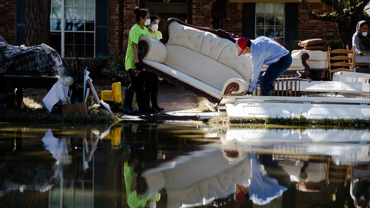 Homeowner Sohail Soomro, center right, accompanied by his family dumps flood damaged furniture on his front yard in the aftermath of Hurricane Harvey on Thursday, Sept. 7, 2017, at the Canyon Gate community in Katy, Texas. (AP Photo/Matt Rourke)