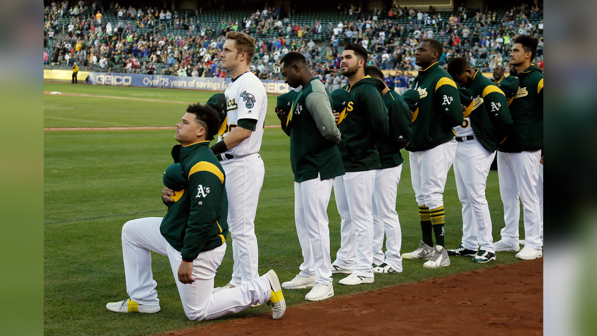 Oakland Athletics catcher Bruce Maxwell kneels during the National Anthem before the start of a baseball game against the Texas Rangers Saturday, Sept. 23, 2017, in Oakland, California.