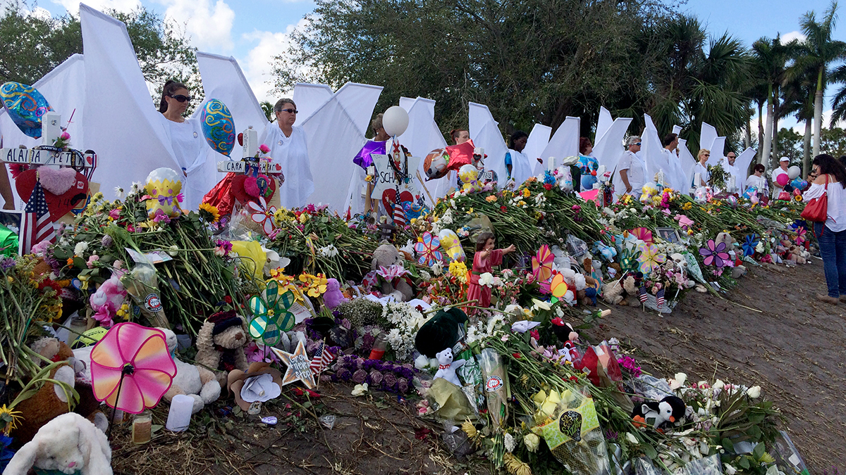 "Seventeen people dressed as angels stand Sunday, Feb. 25, 2018, at the memorial outside Marjory Stoneman Douglas High School in Parkland, Fla., for those killed in a shooting on Feb. 14. Organizer Terry Decarlo said the idea originated after the death of University of Wyoming student Matthew Shepard, who was tortured and murdered in 1998. Decarlo said the costumes now travel to disasters and mass shootings around the country. ""We want to the survivors to know angels are looking over them and protecting them,"" Decarlo said."