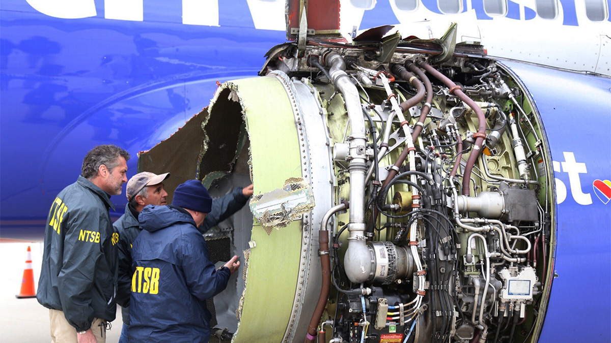 National Transportation Safety Board investigators examine damage to the engine of the Southwest Airlines plane that made an emergency landing at Philadelphia International Airport in Philadelphia on Tuesday, April 17, 2018. The Southwest Airlines jet blew the engine at 32,000 feet and got hit by shrapnel that smashed a window, setting off a desperate scramble by passengers to save a woman from getting sucked out. She later died, and seven others were injured. (NTSB via AP)