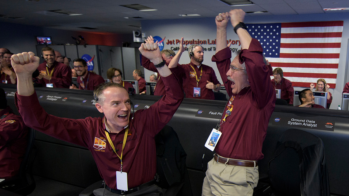 In this image provided by NASA, Mars InSight team members Kris Bruvold, left, and Sandy Krasner rejoice, Monday, Nov. 26, 2018, inside the Mission Support Area at NASA's Jet Propulsion Laboratory in Pasadena, Calif., after receiving confirmation that the Mars InSight lander successfully touched down on the surface of Mars. (Bill Ingalls/NASA via AP)