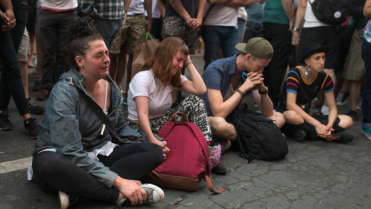 People cry in front of a makeshift memorial to remember the victims of a mass shooting in Orlando, Fla., in New York, Sunday, June 12, 2016. A gunman wielding an assault-type rifle and a handgun opened fire inside a crowded gay nightclub early Sunday before dying in a gunfight with SWAT officers. (AP Photo/Andres Kudacki)