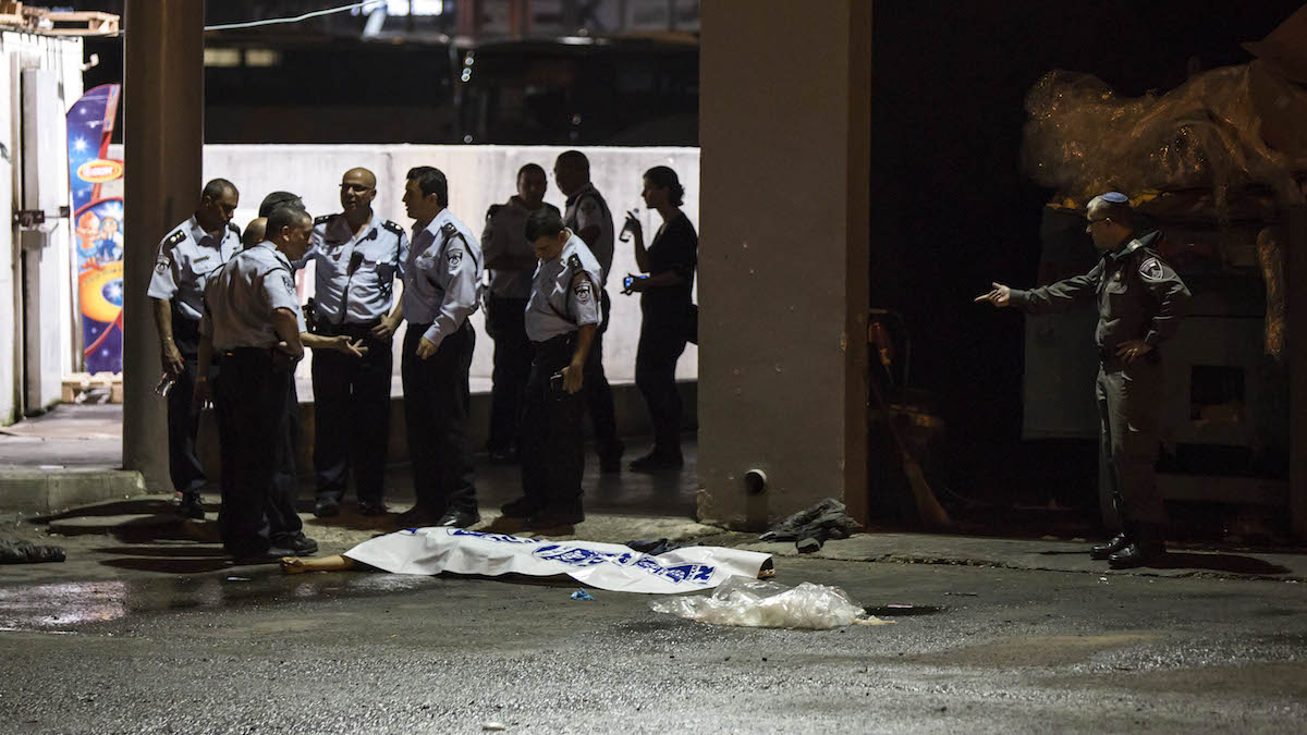Israeli police stand by the shrouded body of Palestinian attacker in Beersheba, Israel, Sunday, Oct. 18, 2015.