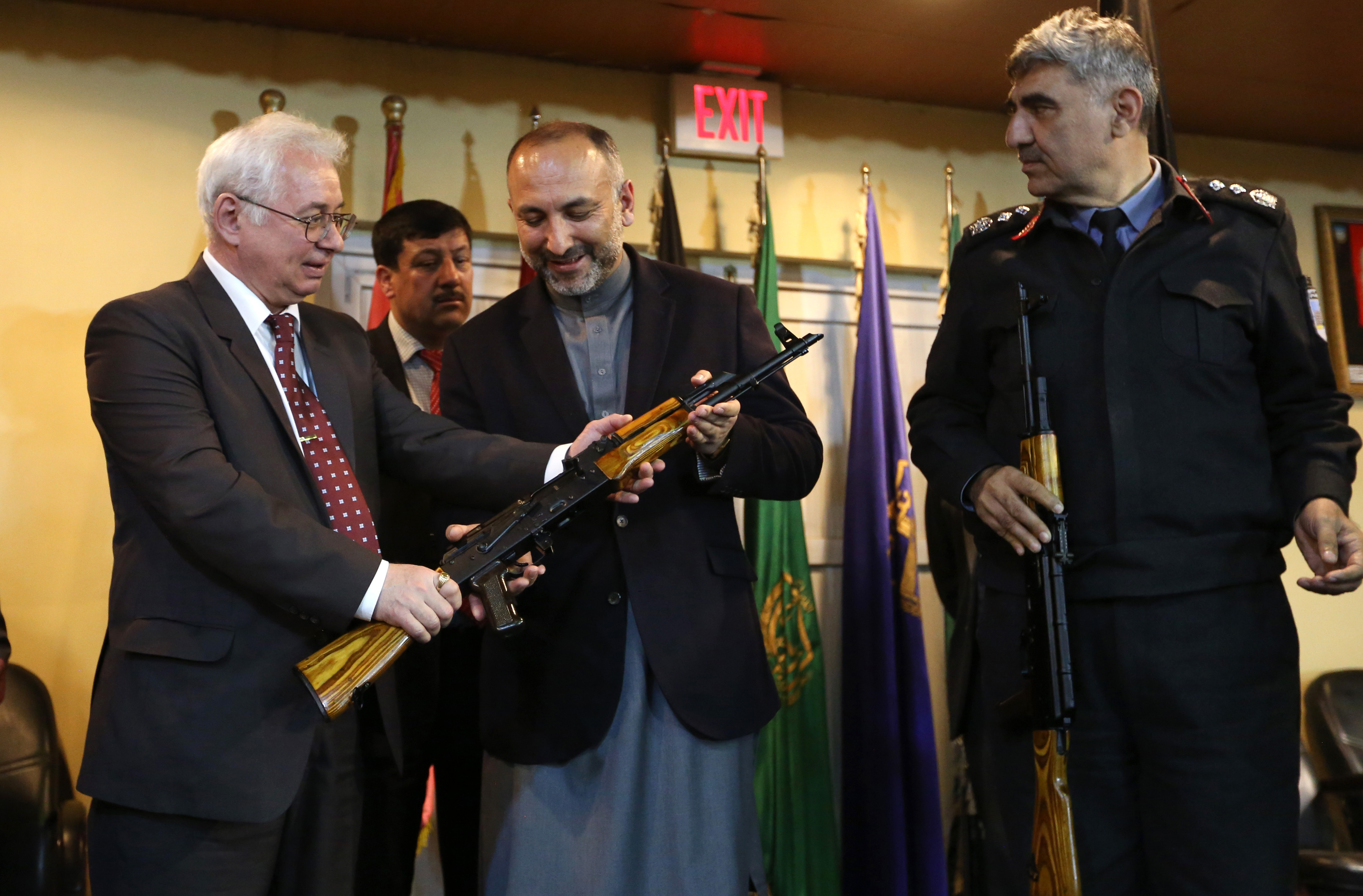 Russian Federation Ambassador, Alexander Mantytskiy, left, hands over an AK-47 to Afghan National Security Advisor, Mohammad Hanif Atmar, center, as the symbol of his country's military donation to the Afghan government, at Kabul International Airport, Wednesday, Feb. 24, 2016. The Russian embassy in Kabul announced that the Russian government handed over 10,000 AK47s as a military donation to Afghan National Security Forces. (AP Photo/Rahmat Gul)