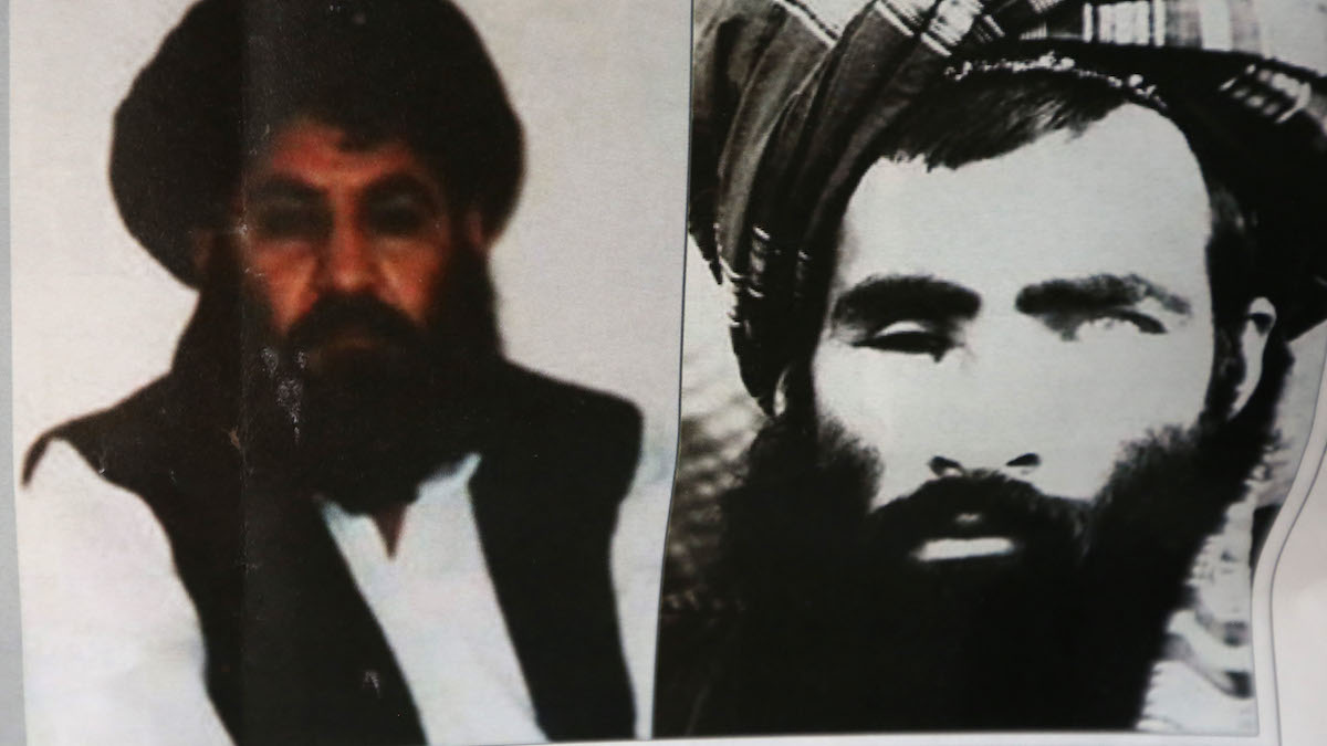 FILE - In this Saturday, Aug. 1, 2015 file photo, an Afghan newspaper headlines pictures of the new leader of the Afghan Taliban, Mullah Akhtar Mansoor, left, and former leader Mullah Mohammad Omar, in Kabul, Afghanistan.