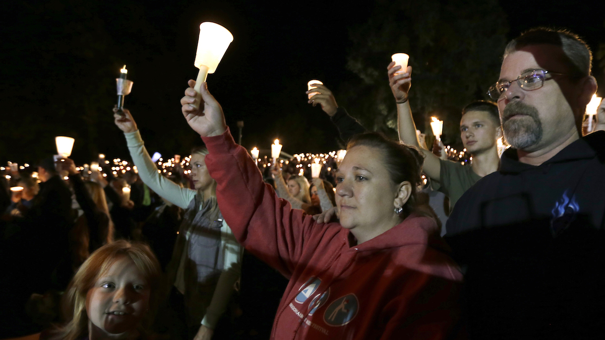 Mourners hold up candles during a candle light vigil at Stewart Park, in Roseburg, Ore., for those killed during a fatal shooting at nearby Umpqua Community College, Thursday, Oct. 1, 2015.