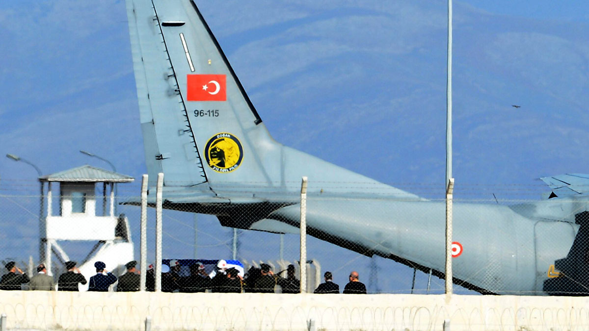 Turkish army officers salute as Turkish honour guard carry the coffin of Russian pilot Lt. Col. Oleg Peshkov into a Turkish Air force transport plane at Hatay airport, Turkey, Sunday, Nov. 29, 2015.  The body of a Russian pilot whose plane was shot down by Turkish jets last Tuesday was placed on a plane in Hatay, Turkey, to be flown home on Sunday.