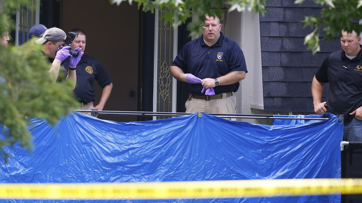 An investigator photographs behind a tarp in the front yard of a home in Broken Arrow, Okla., Thursday, July 23, 2015, where five people were discovered stabbed to death. Two teenagers were taken into custody.