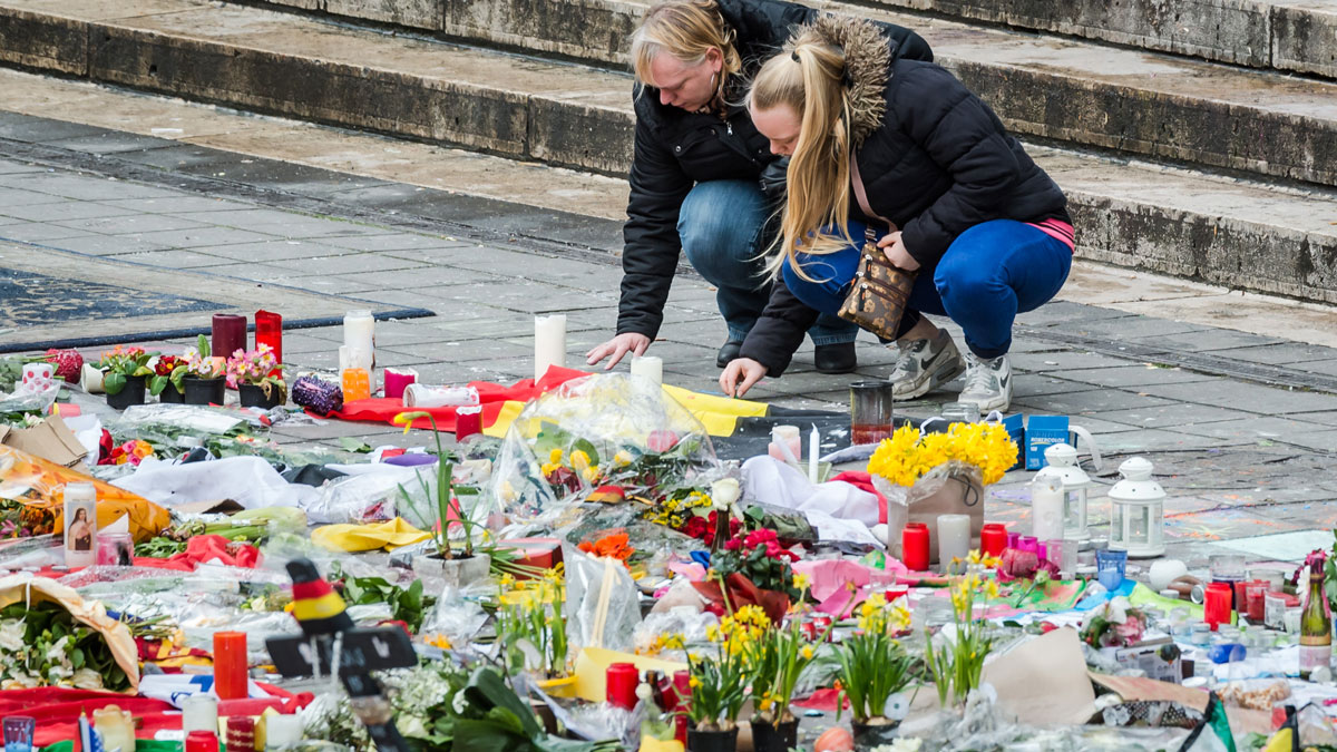 Two women read a solidarity message at floral tributes at a memorial site at the Place de la Bourse in Brussels, Sunday, March 27, 2016.