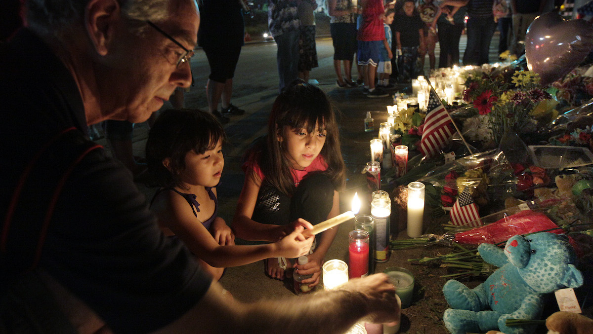 Ted Engelmann, left, helps Yamilet Ortega, 3, second from left, and Kimberly Hernandez, 7, light candles, Saturday, July 21, 2012, at a memorial near the movie theater in Aurora, Colo. where a gunman killed at least 12 people and wounded dozens of others Friday in one of the deadliest mass shootings in recent U.S. history. (AP Photo/Ted S. Warren)