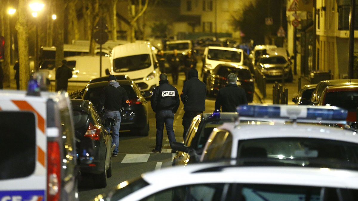 Police officers block a street in Argenteuil, northwest of Paris, late Thursday March 24, 2016 as security forces locked down the area during a major search, France's interior minister said.
