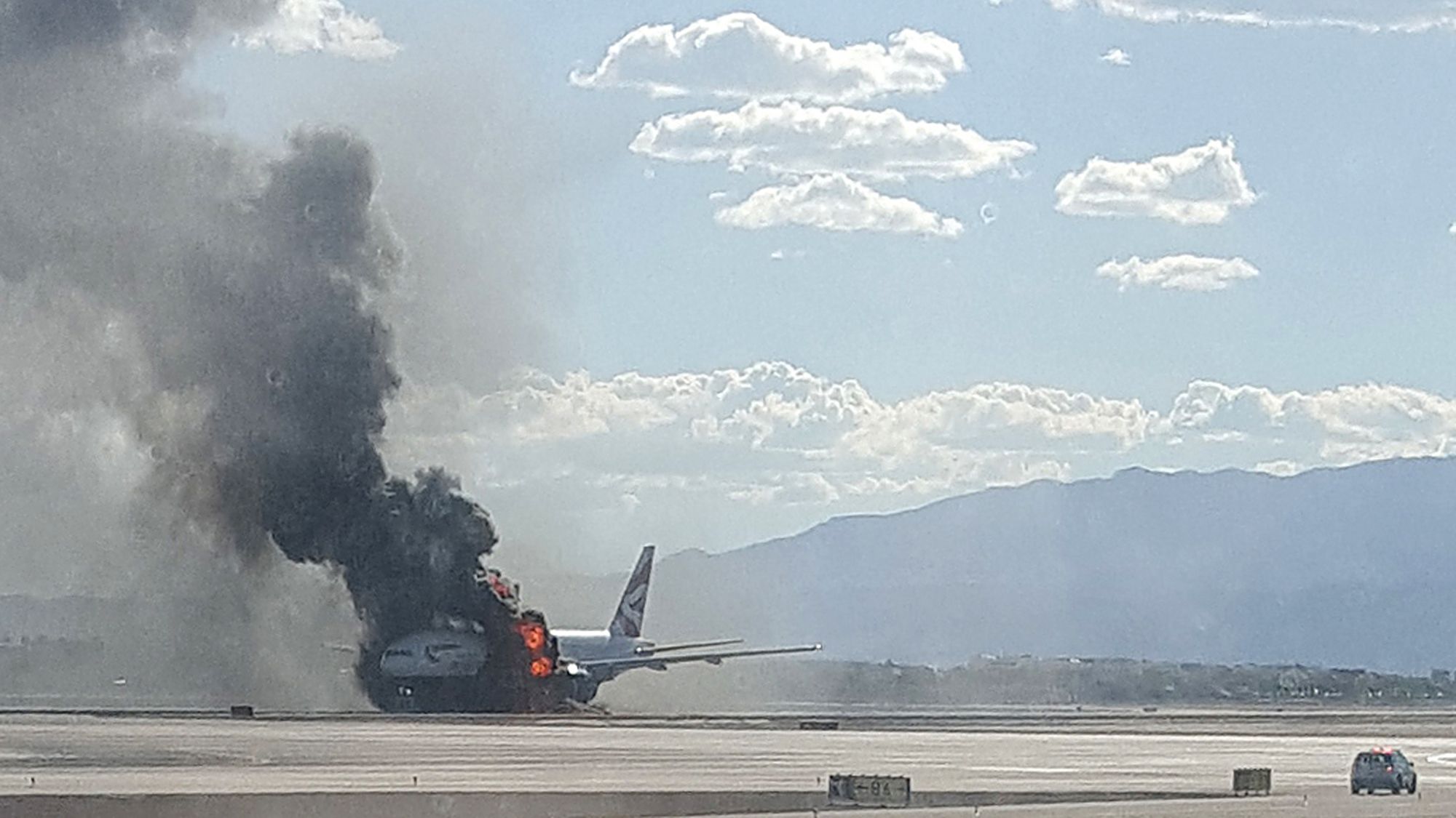 In this photo taken from the view of a plane window, smoke billows out from a plane that caught fire at McCarren International Airport, Tuesday, Sept. 8, 2015, in Las Vegas. An engine on the British Airways plane caught fire before takeoff, forcing passengers to escape on emergency slides.
