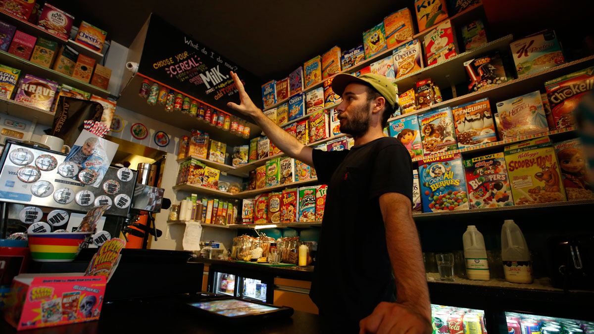 A member of staff of the Cereal Killer Cafe helps point out to a customer the range of cereals available from US favourites to European gluten free organics at the cafe in Brick Lane, London, Wednesday, Sept. 30, 2015.