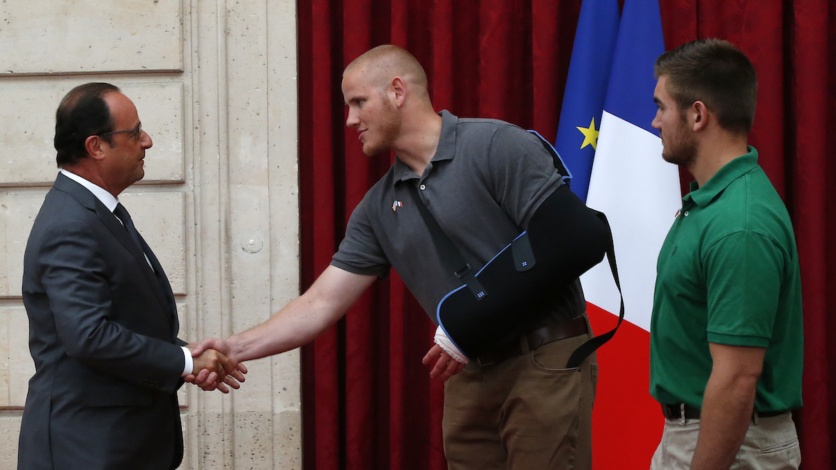 French President Francois Hollande, left, shakes hands with U.S. Airman Spencer Stone, as U.S. National Guardsman from Roseburg, Oregon, Alek Skarlatos, right, looks on at the Elysee Palace, Monday Aug.24, 2015 in Paris, France. Three Americans and a British man who took down a heavily armed man on a passenger train speeding through Belgium have received France's top honor.