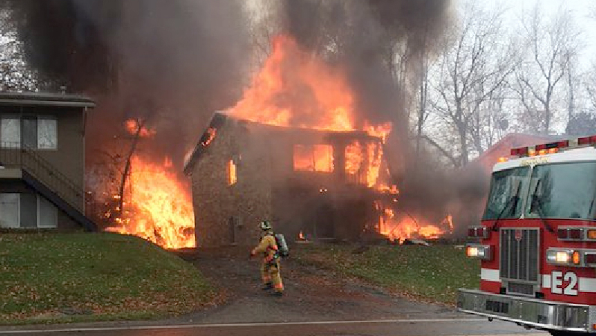 A firefighter walks up a driveway as an apartment building burns in Akron, Ohio, Tuesday, Nov. 10, 2015, where authorities say a small business jet crashed. The plane burst into flames and disintegrated after impact. It was unclear how many people were on board.
