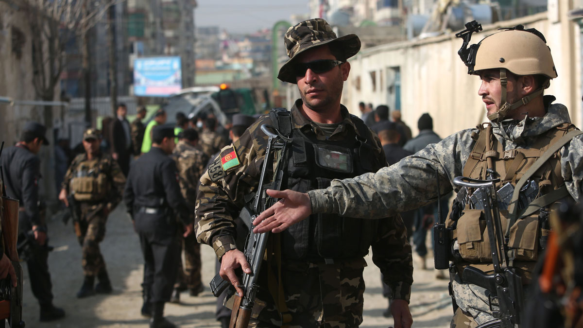 Afghan security forces inspect the site of a suicide attack in Kabul, Afghanistan, Saturday, Nov. 28, 2015. Afghanistan's election commission says one of its officials escaped unharmed after a suicide bomber targeted his vehicle in the capital, Kabul, killing his bodyguard and wounding his driver.