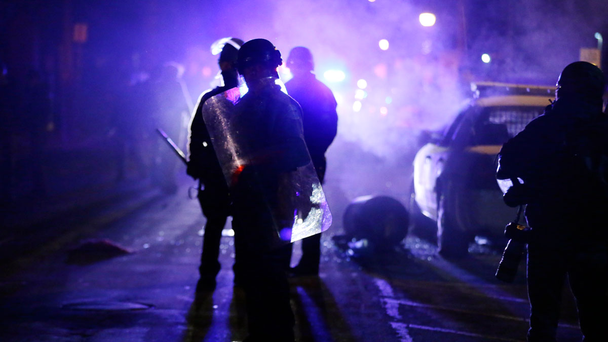 FILE - In this Nov. 25, 2014 file photo, police officers watch protesters as smoke fills the streets in Ferguson, Mo. after a grand jury's decision in the fatal shooting of Michael Brown.