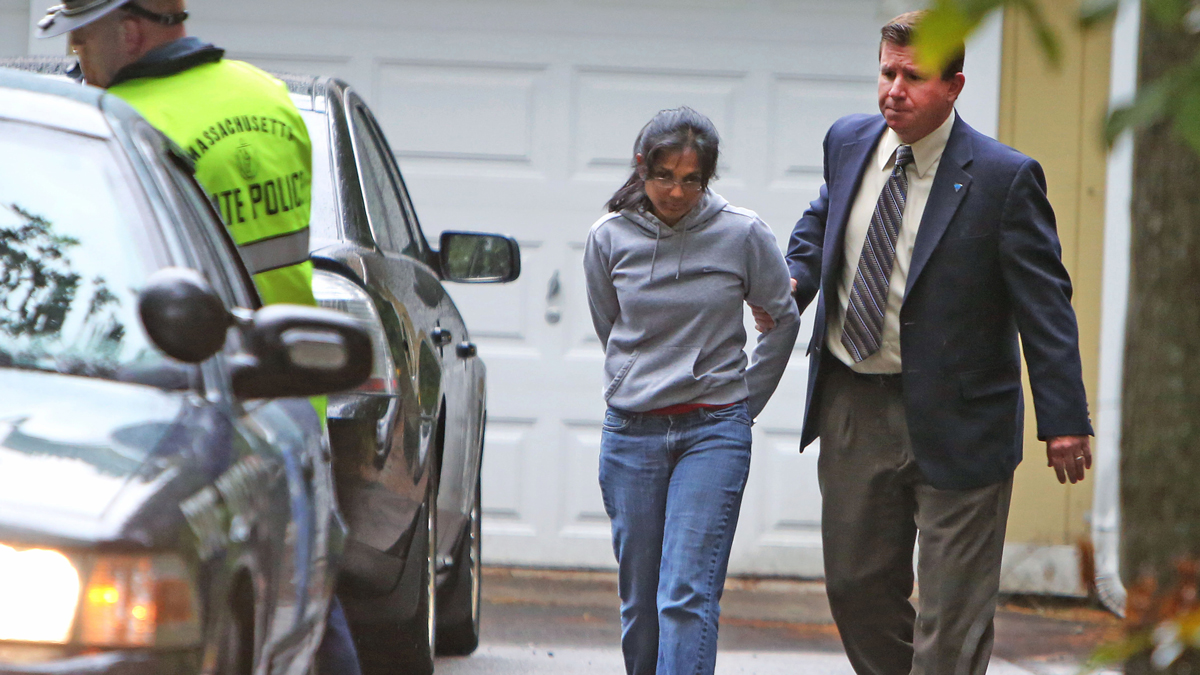 In this Sept. 28, 2012 file photo, Annie Dookhan, center, is escorted to a cruiser outside her home in Franklin, Mass. Dookhan is accused of faking drug results, forging signatures and mixing samples a state police lab. State police say Dookhan tested more than 60,000 drug samples involving 34,000 defendants during her nine years at the lab in one of Massachusetts's top stories in 2012. (AP Photo/Bizuayehu Tesfaye, File)