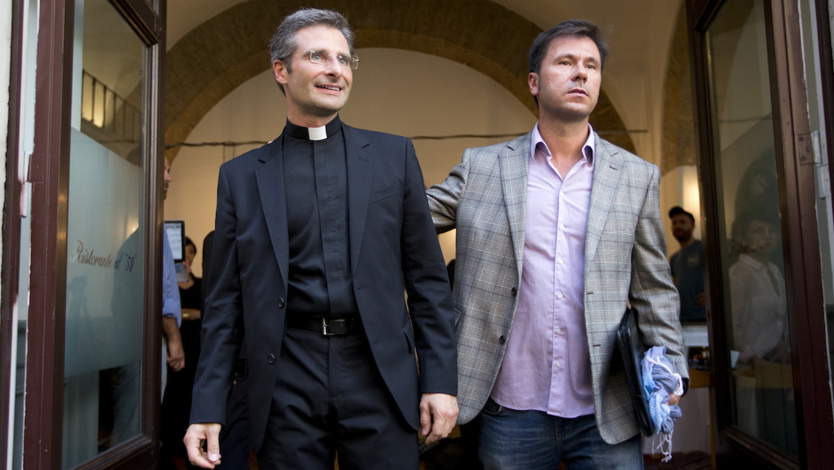 Monsignor Krzysztof Charamsa, left, and his boyfriend Eduard, surname not given, pose for a photo as they leave a restaurant after a press conference in downtown Rome, Saturday Oct. 3, 2015.