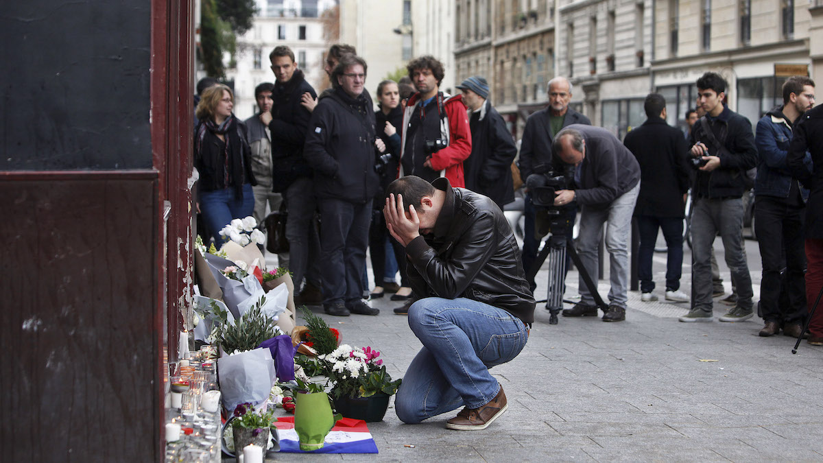 A man holds his head in his hands as he lays flowers in front of the Carillon cafe, in Paris, Saturday, Nov.14, 2015. French President Francois Hollande vowed to attack Islamic State without mercy as the jihadist group admitted responsibility Saturday for orchestrating the deadliest attacks inflicted on France since World War II.