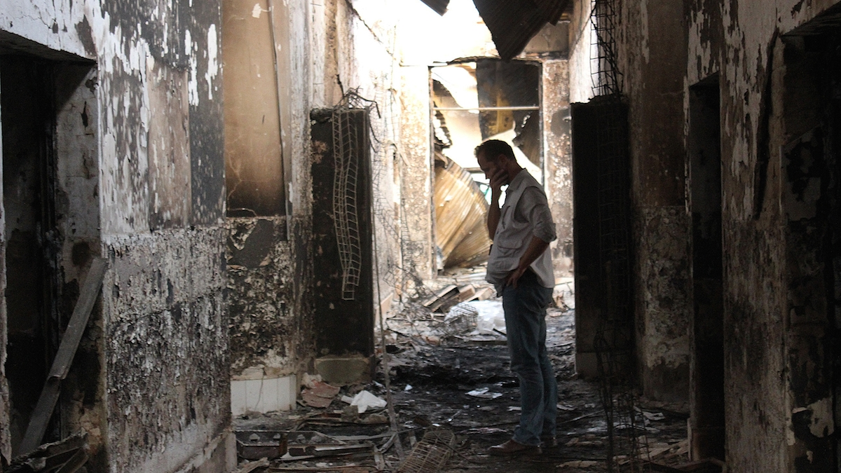 "In this Friday, Oct. 16, 2015 photo, an employee of Doctors Without Borders walks inside the charred remains of their hospital after it was hit by a U.S. airstrike in Kunduz, Afghanistan. Christopher Stokes, general director of Doctors Without Borders, which is also known by its French abbreviation MSF, whose hospital in northern Afghanistan was destroyed in a U.S. airstrike, says the ""extensive, quite precise destruction"" of the bombing raid casts doubt on American military assertions that it was a mistake."