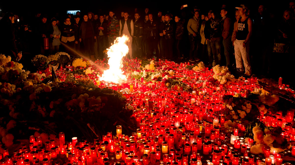 People stand by burning candles outside the compound that housed a nightclub where a fire occurred in the early Saturday in Bucharest, Romania, to pay respects to the victims, marking 24 hours after the accident Sunday, Nov. 1, 2015. Flames spread quickly through the crowded basement club, trapping many and triggering a stampede, making it the deadliest nightclub blaze in Romanian history.
