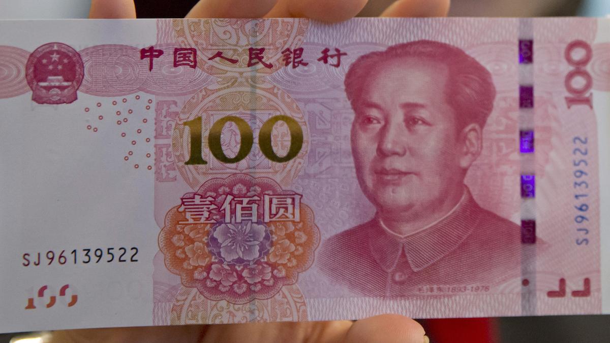 A staff member displays the new version of the 100-yuan RMB banknotes at the Bank of China Tower in Hong Kong, Thursday, Nov. 12, 2015.