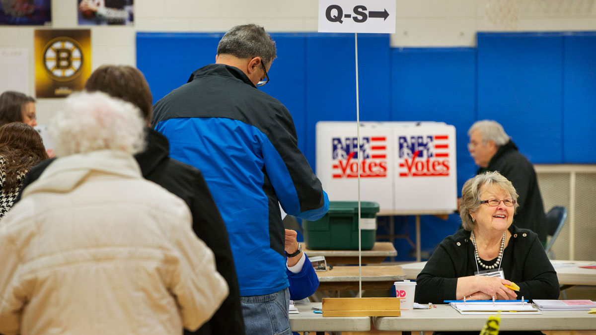 Brooks Thompson, right, checks voters in at a polling place at Broad Street Elementary in Nashua, N.H., Tuesday, Feb. 9, 2016, during the New Hampshire primary.
