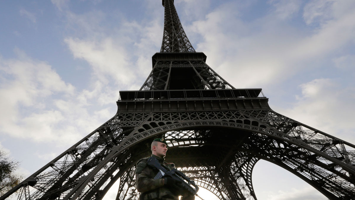 A French soldier stands alert at the Eiffel Tower which remained closed on the first of three days of national mourning in Paris, Sunday, Nov. 15, 2015.