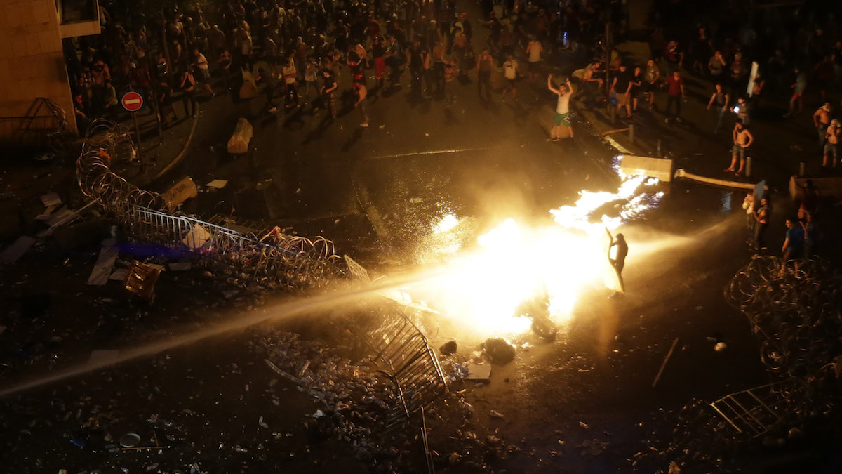 Lebanese protesters set a police motorcycle on fire as they are sprayed by riot police using water cannons during a protest against the ongoing trash crisis, in downtown Beirut, Lebanon, Sunday, Aug. 23, 2015. Lebanese riot police fired several rounds of tear gas and water cannons for the second consecutive day in downtown Beirut Sunday as they battled protesters with batons and stones _ a marked escalation of mass demonstrations against an ongoing trash crisis. (AP Photo/Hassan Ammar)