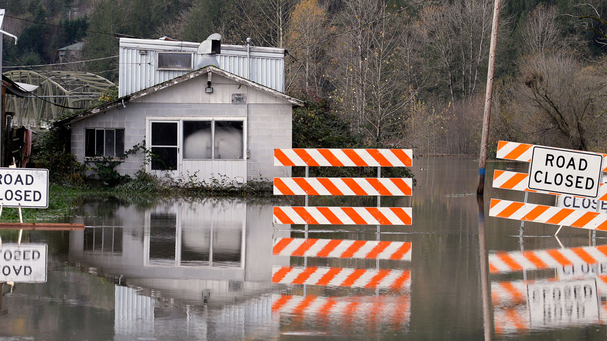 A building sits just above flood waters and at a closed road from flooding, Wednesday, Nov. 18, 2015, in Carnation, Washington.