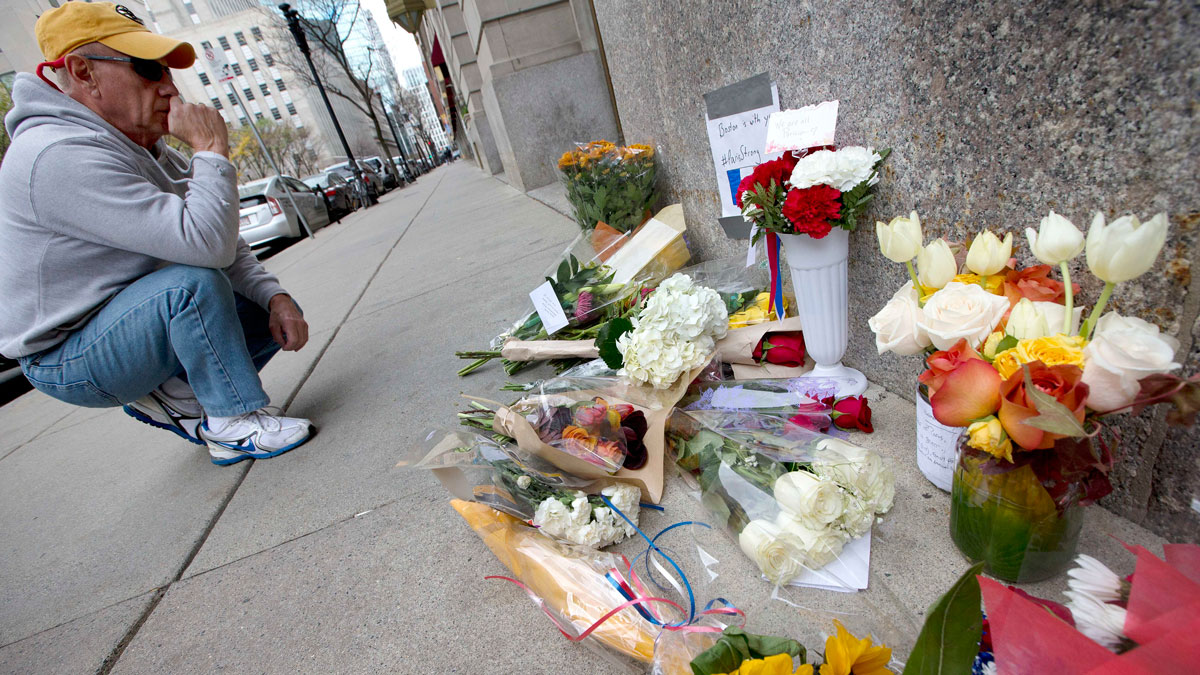 An unidentified man pauses after placing flowers on a make-shift memorial outside the French Consulate in Boston, Saturday, Nov. 14, 2015. French officials say several dozen people were killed in shootings and explosions at a theater, restaurant and elsewhere in Paris on Friday.