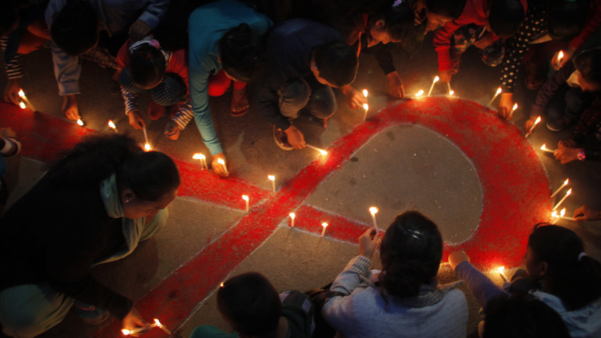 """Nepalese women and children from """"Maiti Nepal"""", a rehabilitation center for victims of sex trafficking, light candles on the eve of World Aids Day in Kathmandu, Nepal, Monday, Nov. 30, 2015. World AIDS Day is observed on December 1 every year to raise the awareness in the fight against HIV."""