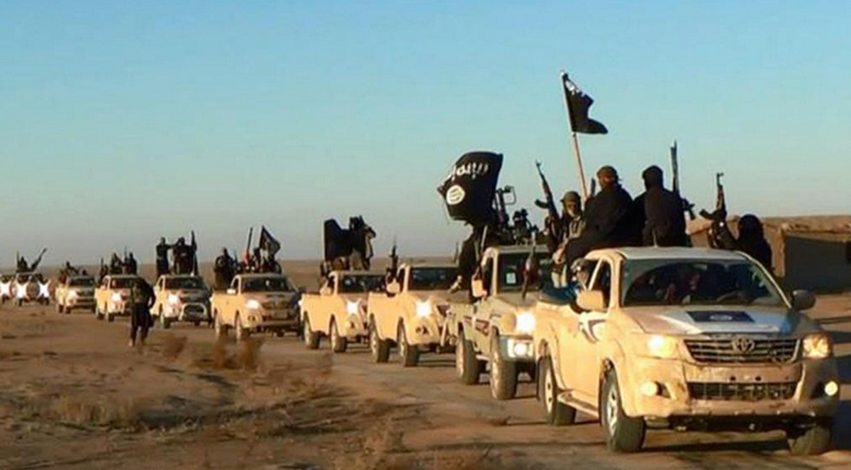 In this undated file photo released by a militant website, which has been verified and is consistent with other AP reporting, militants of the Islamic State group hold up their weapons and wave flags as they ride in a convoy, which includes multiple Toyota pickup trucks, through Raqqa city in Syria on a road leading to Iraq. Toyota is working with U.S. officials after questions were raised about the prominent use of its vehicles by militant organizations in Syria, Iraq and Libya.