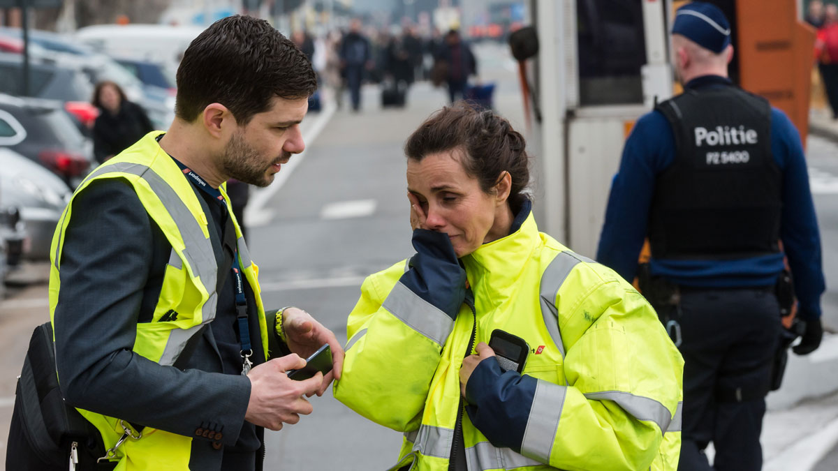 People react outside Brussels airport after explosions rocked the facility in Brussels, Belgium Tuesday March 22, 2016. Explosions rocked the Brussels airport and the subway system Tuesday, just days after the main suspect in the November Paris attacks was arrested in the city, police said. (AP Photo/Geert Vanden Wijngaert)