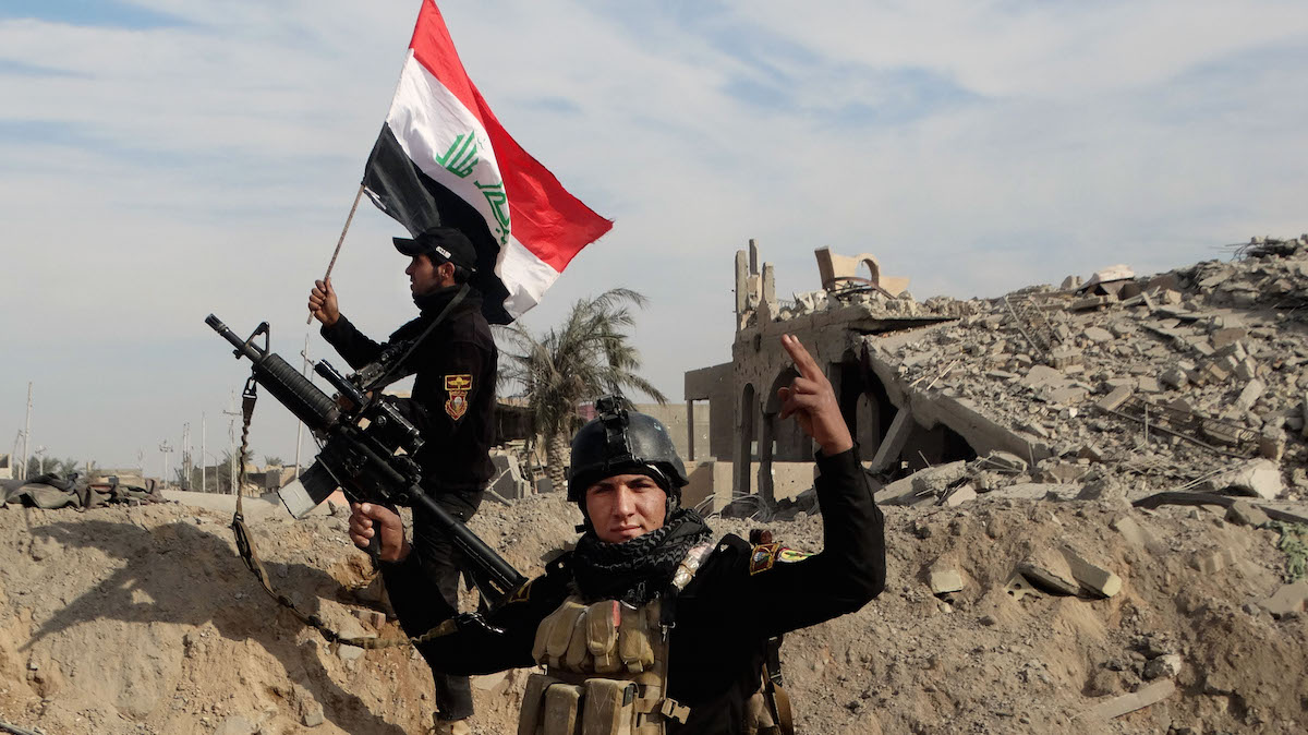 In this Sunday, Dec. 27, 2015 photo, Iraqi security forces raise an Iraqi flag near the provincial council building in central Ramadi, 70 miles (115 kilometers) west of Baghdad. Iraqi military forces on Monday retook a strategic government complex in the city of Ramadi from Islamic State militants who have occupied the city since May.