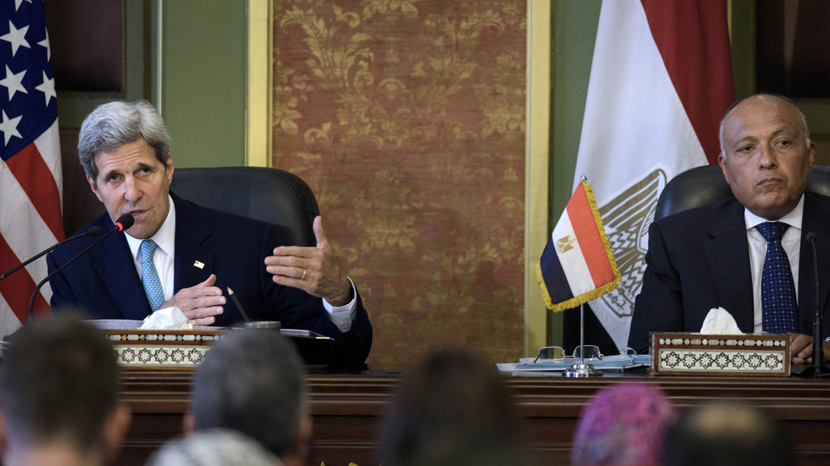 Egypt's Foreign Minister Sameh Shoukry, right, listens to U.S. Secretary of State John Kerry deliver a speech during a press conference after their meeting at the foreign ministry in Cairo, Egypt, Sunday, Aug. 2, 2015. The United States and Egypt on Sunday resumed formal security talks that were last held six years ago and kept on hiatus until now amid the political unrest that swept the country in the wake of the Arab Spring.