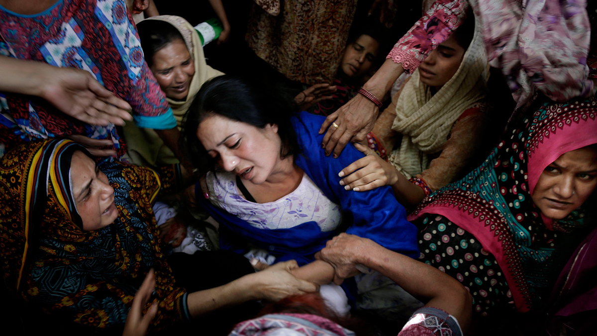 Women try to comfort a mother who lost her son in an Easter Sunday bomb attack in Lahore, Pakistan, March 28, 2016.