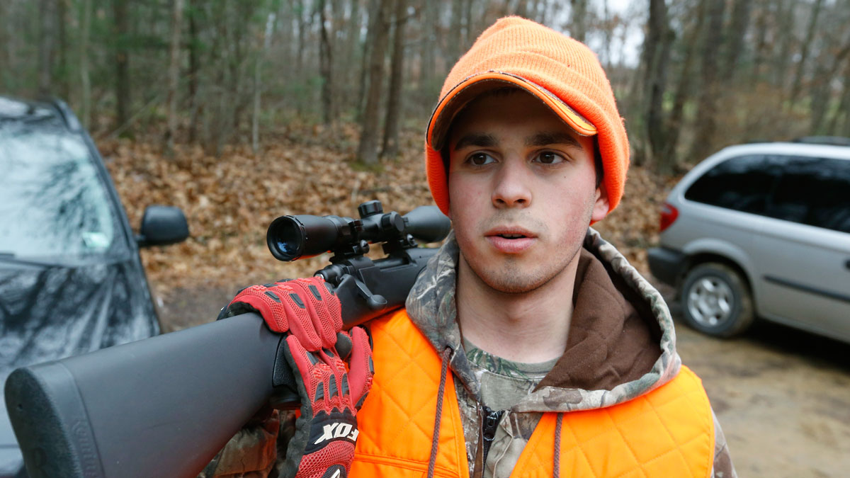 Aaron Rech, of Hampton Township, holds his rifle over his shoulder after coming out of the woods during the first day of Pennsylvania's white-tailed deer hunting season Monday, Dec. 1, 2014, on the state game lands in Butler, Pa.