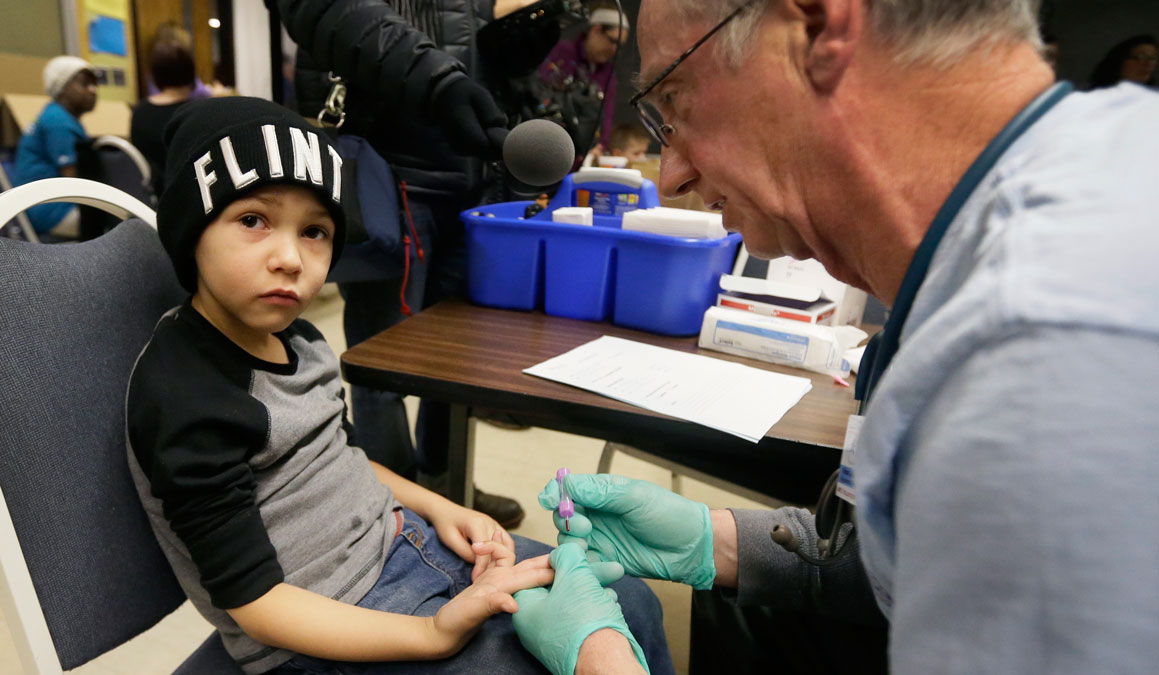 Registered Nurse Brian Jones draws a blood sample from Grayling Stefek, 5, at the Eisenhower Elementary School, Tuesday, Jan. 26, 2016 in Flint, Mich. The students were being tested for lead after the metal was found in the city's drinking water.