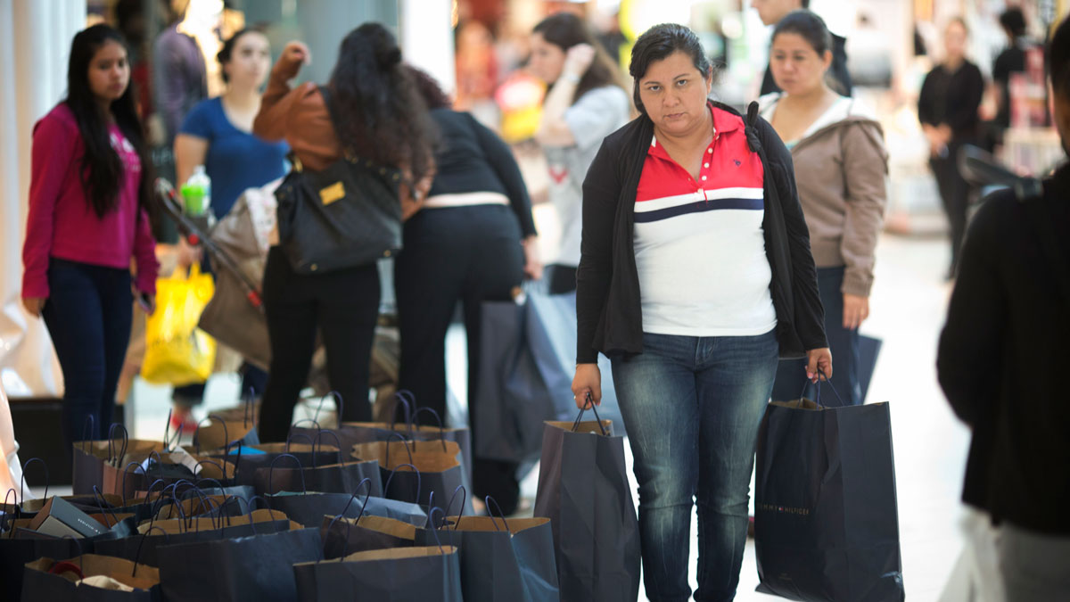 File photo: A shopper carries some of the clothes she bought at a Tommy outlet store at Dolphin Mall in Sweetwater, Florida, Friday, Nov. 28, 2014.