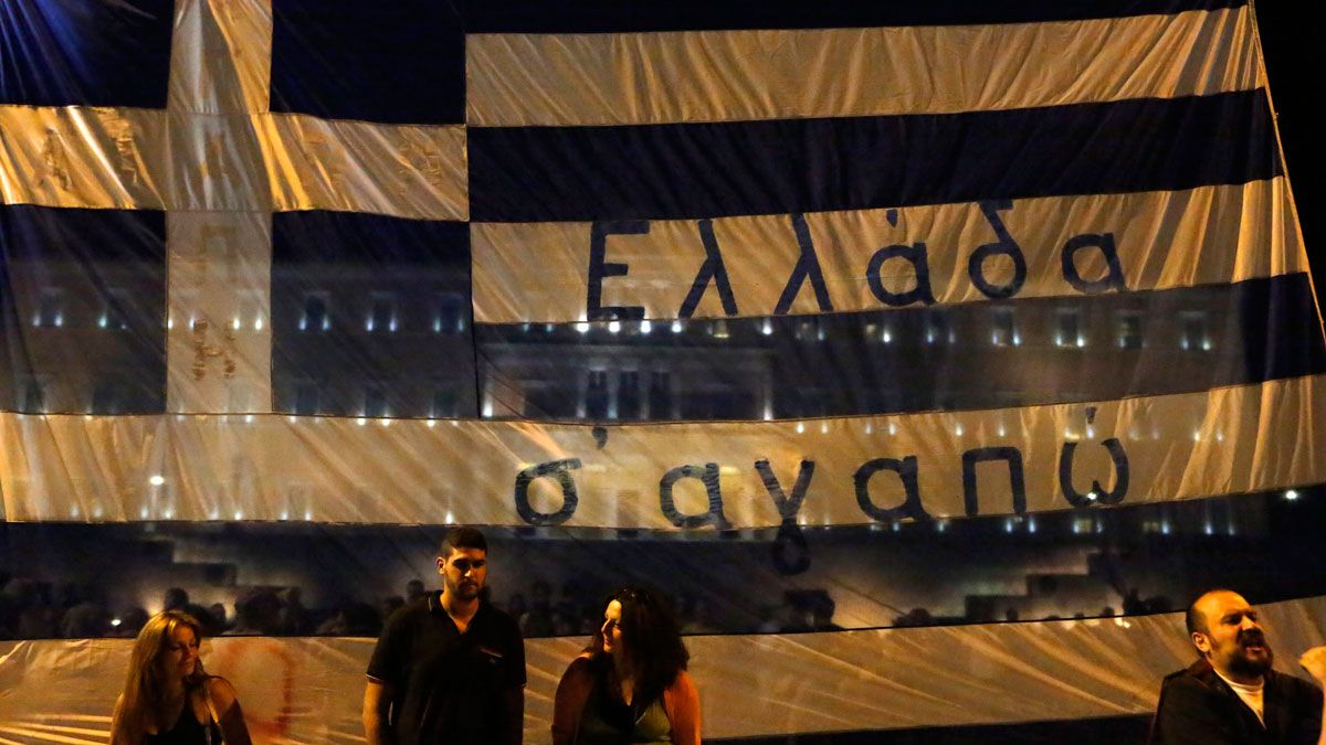 Anti-austerity protesters stand in front of a Greek flag reading ''Greece we love you'' during a rally outside the Greek Parliament in Athens, Wednesday, July 15, 2015. Greece's prime minister was fighting to keep his government intact in the face of outrage over an austerity bill that parliament must pass Wednesday night if the country is to start negotiations on a new bailout and avoid financial collapse.