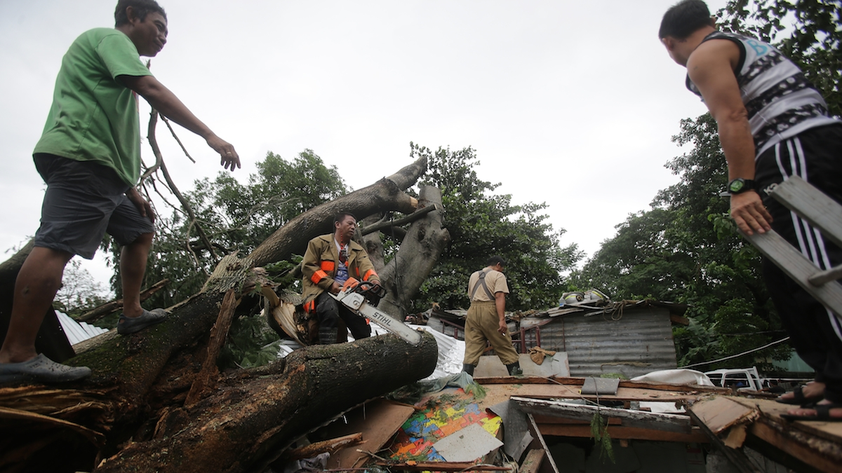 Residents and rescuers cut up a fallen tree on top of damaged a house from Typhoon Koppu in suburban Quezon city, north of Manila, Philippines on Monday, Oct. 19, 2015. Army, police and civilian volunteers scrambled Monday to rescue hundreds of villagers trapped in their flooded homes and on rooftops in a northern Philippine province battered by slow-moving Typhoon Koppu.