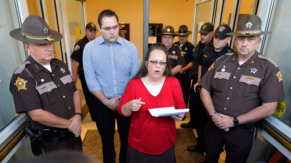 Surrounded by Rowan County Sheriff's deputies, Rowan County Clerk Kim Davis, center, with her son Nathan Davis by her side, makes a statement to the media at the Rowan County Judicial Center in Morehead, Ky., Sept. 14, 2015. Davis announced that her office will issue marriage licenses under order of a federal judge, but they will not have her name or office listed.