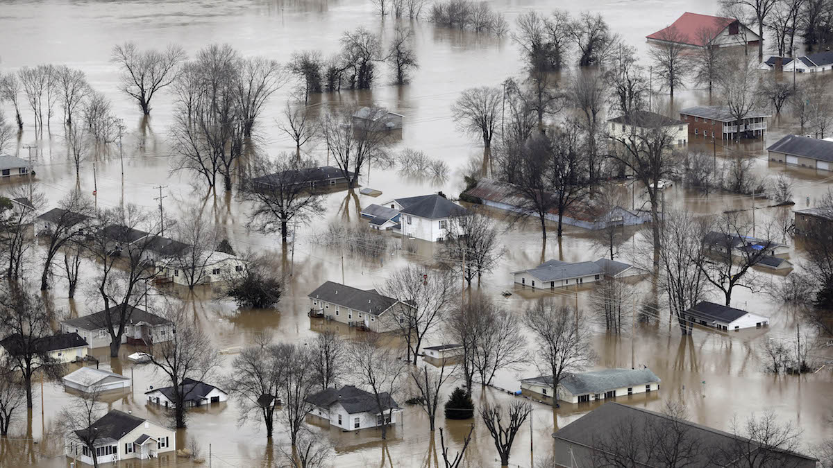 In this aerial photo, homes are surrounded by floodwater, Wednesday, Dec. 30, 2015, in Pacific, Mo. Surging Midwestern rivers forced hundreds of evacuations, threatened dozens of levees and brought transportation by car, boat or train to a virtual standstill Thursday in the St. Louis area.