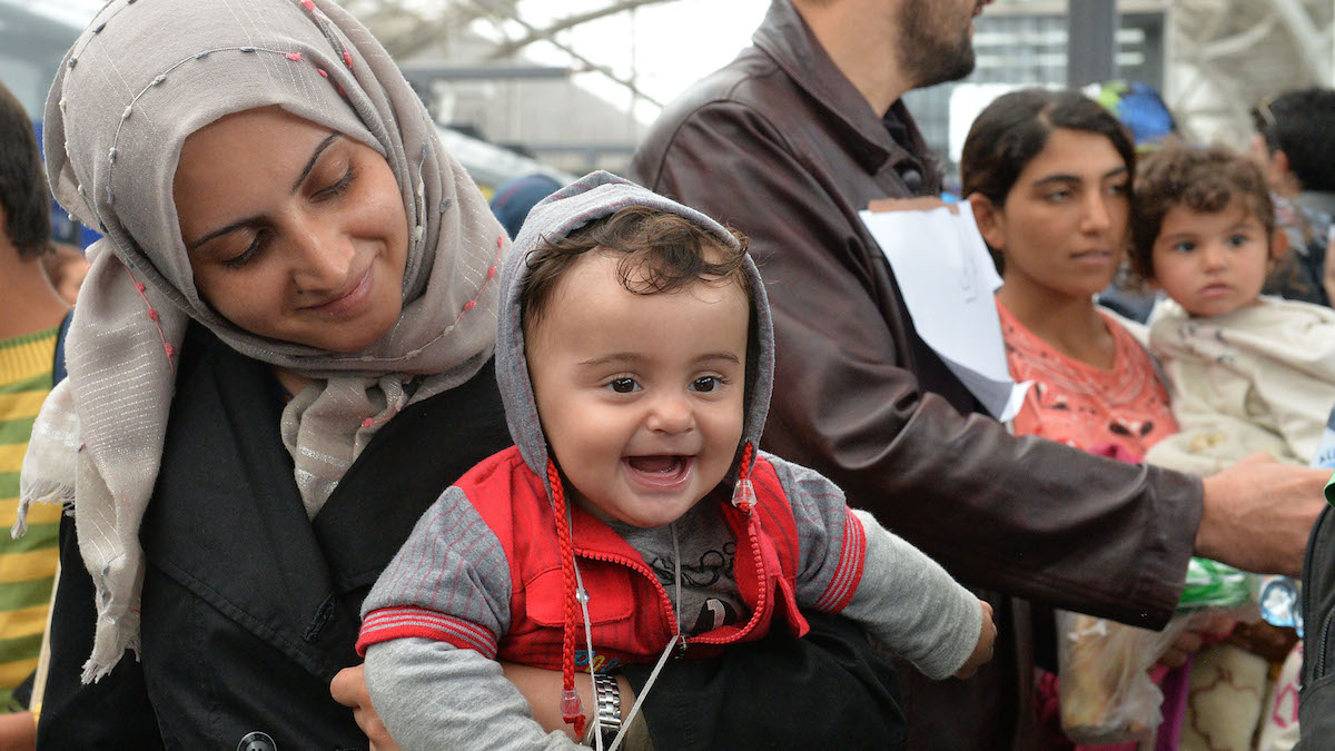 A woman holds her smiling baby in her arms as she arrives  at the Hauptbahnhof station in Salzburg, Austria, Saturday, Sept. 5, 2015 on their way from Hungary via Vienna to Germany.